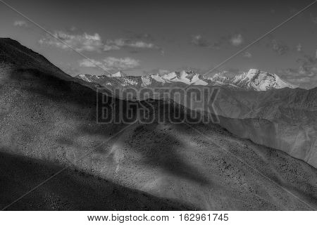 Rocky landscape of Ladakh at Changla pass play of light and shodow on the mountain Leh Ladakh Jammu and Kashmir India. Black and white image.