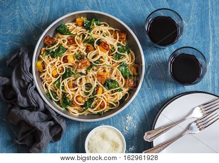 Baked pumpkin and spinach spaghetti in a frying pan and two glasses of red wine on wooden background top view. Delicious lunch in a mediterranean style. Flat lay