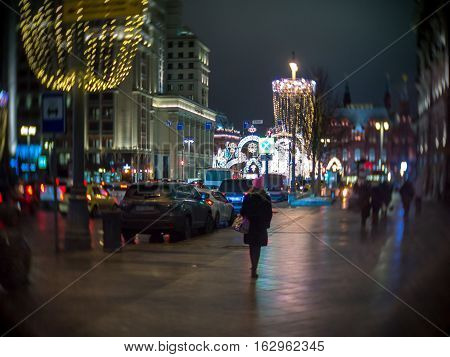 Girl in pink hat walks along the Christmas decorated Tverskaya street view of the hotel Moscow in night