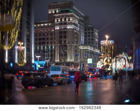 Woman in red walk along the Christmas decorated Tverskaya street view of the hotel Moscow in night