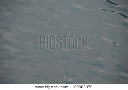 the water surface of a lake or river, river water surface texture, The blue surface of an alpine lake with light waves.
