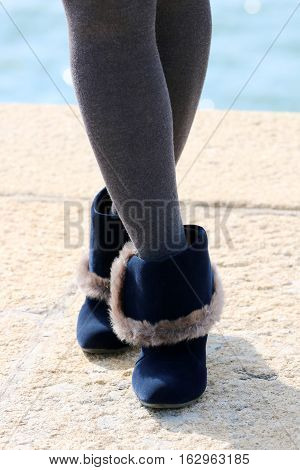 Woman with legs in gray stockings and ankle boots, Winter fashion outfit