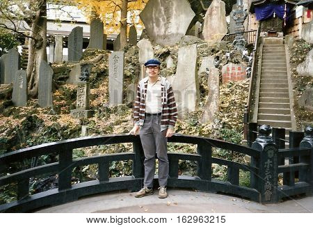 NARITA, CHIBA / JAPAN - CIRCA NOVEMBER, 1987: An American tourist poses for a photograph in front of prayer stones near the Niomon Gate in the Narita-san  Shinshō-ji Shingon Buddhist temple.