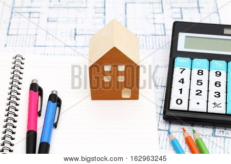 Miniature  model of house and blueprints, construction plan