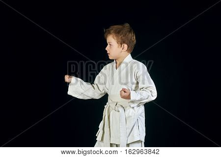 Young boy in kimono shows the martial arts on a black background