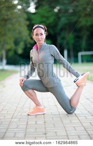 runner doing stretching exercises outdoors. Attractive girl stretching before Fitness and Exercise Outdoor