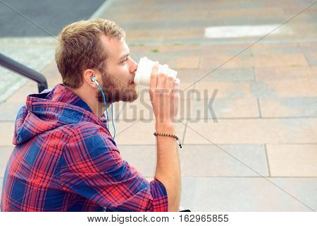 Young Man In Checkered Shirt Sitting On Stairs Listening Musik And Drinking Soft Drink