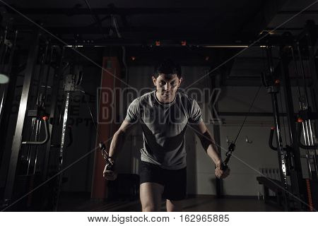 Young Man At The Gym Exercise On The Pectoral Muscles, The Reduction In The Hands Of Crossover. Toni