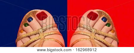 Multicolored shining pedicure on red and blue background closeup.