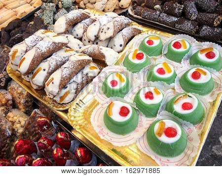 Sicilian food: traditional cannoli and cassata on sale in a street food market.