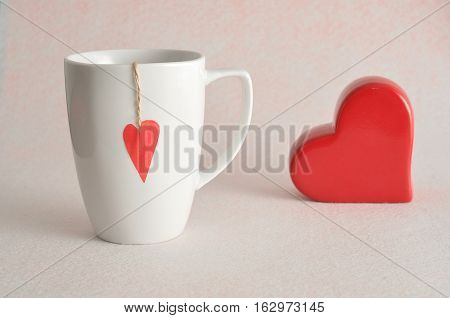 Valentine's Day. A white mug with a red heart attached to a string with a red heart isolated against a white background