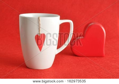 Valentine's Day. A white mug with a red heart attached to a string with a red heart isolated against a red background