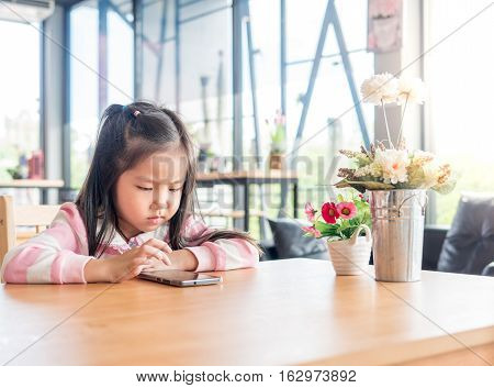 Portrait Of Asia Pretty Little Girl Play Mobile Phone, Serious Feeling