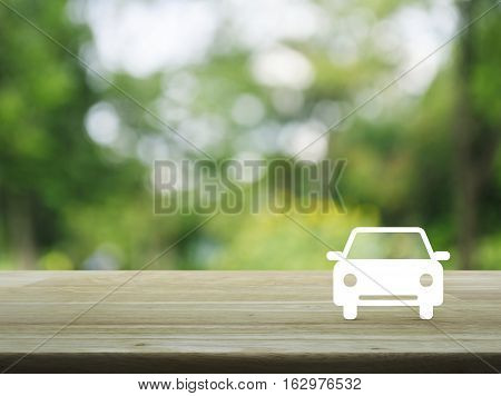 Car flat icon on wooden table over blur green tree background Business service car concept