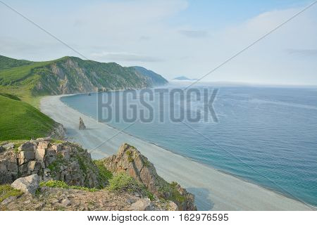 A landscape on sea: seawater rocks fog clouds.