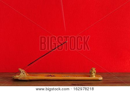 A bamboo incense holder with a incense stick and a Buddha figurine