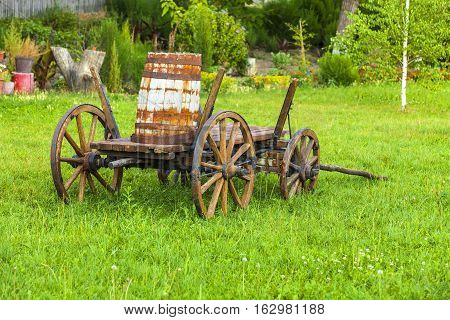 Old wooden cart with a keg on the green grass