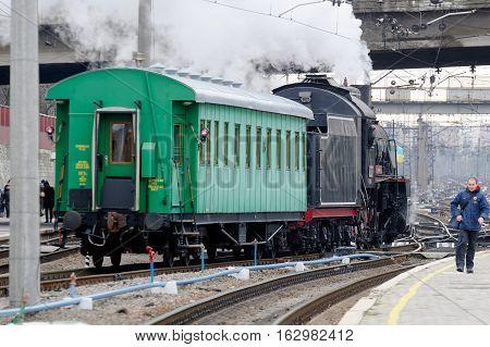 Kharkiv Ukraine - November 4 2016: Restored steam locomotive Er-794-12 and retro passenger car in railway station