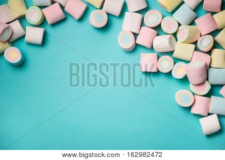 Top view of pastel colored marshmallow on a blue background. Minimalism style.