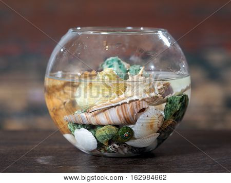Fishbowl with water and a variety of sea shells