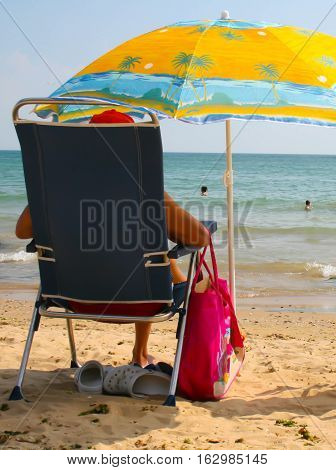 picture of a man sunbathing on a deckchair on the beach