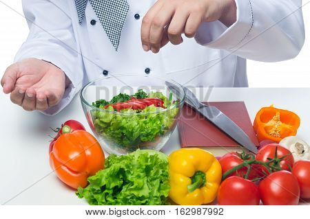 cook adds salt vegetable salad in a bowl on a table