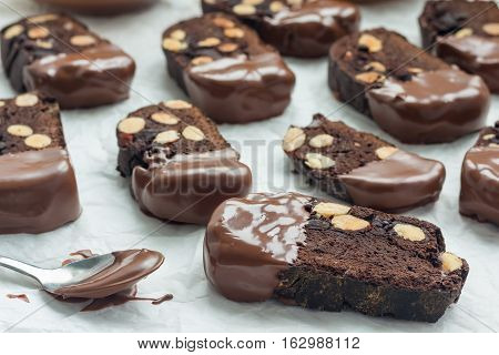 Homemade dark chocolate biscotti cookies with almonds covered with melted chocolate horizontal