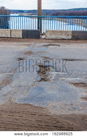 Potholes on the bridge. Bad road. The road to the village is very poorly repaired the pits appear constantly.