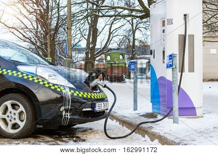 Parnu Estonia - January 10 2016: Electric-taxi brand Nissan fueled electric energy from eco-friendly high-tech charging battery station. Modern technologies of ecological transportation. National Estonian architecture on snowy winter street