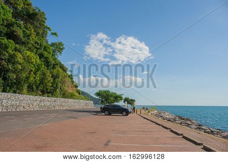 Car parked on car parking at the sea with blue sky background.