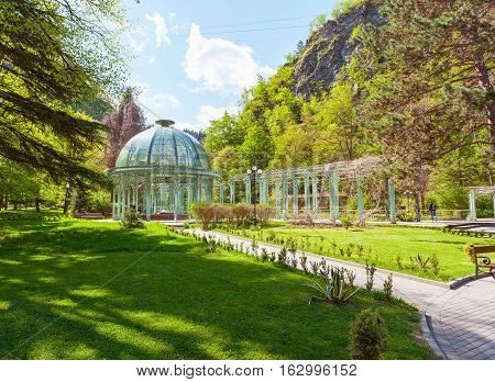 Borjomi Central Historical Park. Georgia. Source with healing mineral water. Beautiful pavilion with a glass dome.
