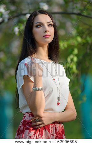 Beautiful yong model wearing luxury jewelry in blooming spring garden