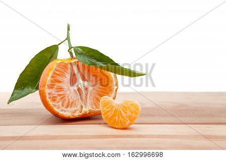 on a wooden plank there is half tangerine whit leaf
