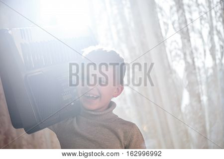 The boy laughs and holds his shoulder synthesizer