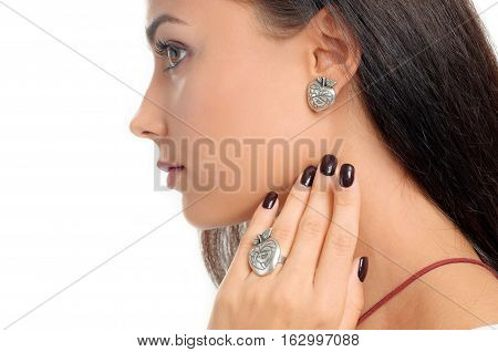 close-up studio portrait model demonstrate stylish finger ring and earring. Spring jewelry collection of silver accessory