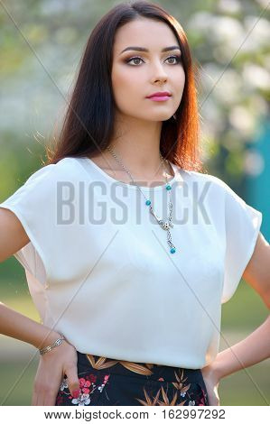 Beautiful young woman with long hair with a beautiful makeup and bracelet posing outdoors. Around her neck is a stylish necklace.