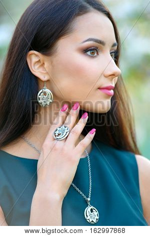 long hair beautiful european woman wearing luxury accessory and jewelry. Close-up beauty portrait outdoors