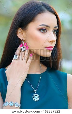 Fashion model beautiful long hair girl with spring collection luxury accessory and jewelry. Perfect view background blooming garden