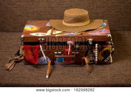 Charges girl to travel. The old suitcase piled disorderly everything that can be useful for rest and recreation