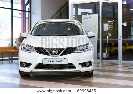 Parnu Estonia - January 10 2016: Nissan Pulsar in the lobby of the shopping centre Port Artur 2. New white Japanese car as a showpiece. Stylish family vehicle at the exhibition car dealer