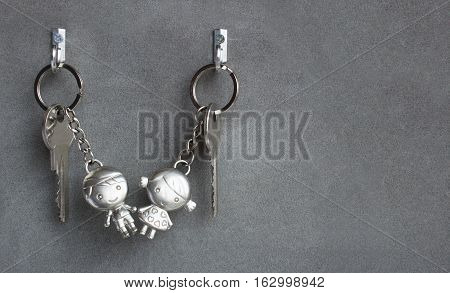 Keyrings boy and girl pulling hands. Lovers keychains, love. Gray background