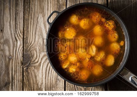 Cooked meatballs in a stewpot on the old boards horizontal copy space
