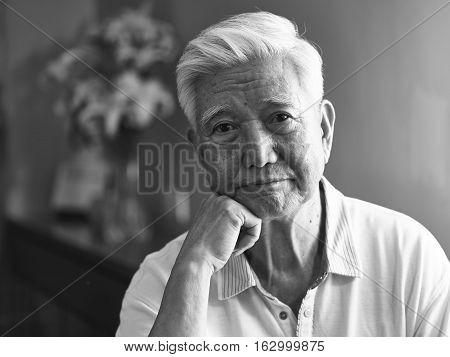 black and white portrait of a sad lonely asian senior hand on chin looking at camera.