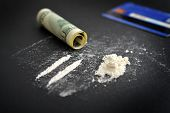 Cocaine drug addiction. Lines of cocaine and one hundred dollars banknote on black background closeup poster