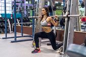 Fit girl doing lunges with the smith machine. poster