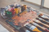 Painter workplace. Palette with brushstrokes and paintbrushes. Colorful gouache, crayons sets. poster
