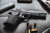 .45 Caliber hollow point bullets near handgun and magazine on leather furniture poster
