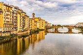 Apartments and bridge on the Arno river with reflections poster