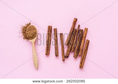 Cinnamon On Pink Background. Ground Cinnamon And Cinnamon Sticks On Pastel Pink Background, Top View