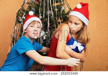 Humorous dispute over a gift box near a decorated Christmas tree poster